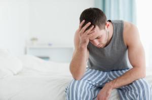 Der Mann sitzt traurig auf seinem Bett und will seine Ex zurückgewinnen.