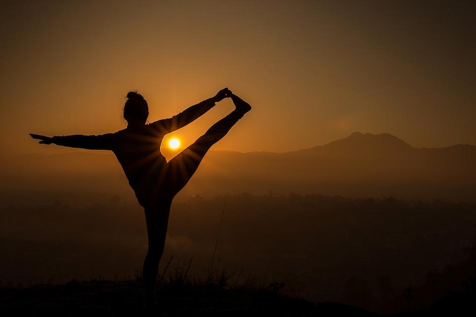Diese Person genießt den morgentlichen Sonnenaufgang während einer Meditationsübung.