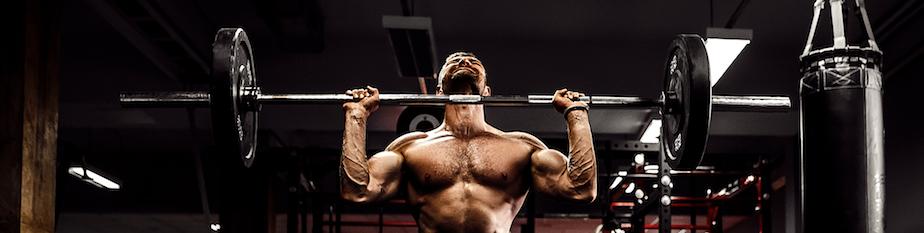 muskuloeser-fitness-mann-der-eine-kreuzhantel-ueber-seinem-kopf-im-modernen-fitness-center-kreuzheben-tut
