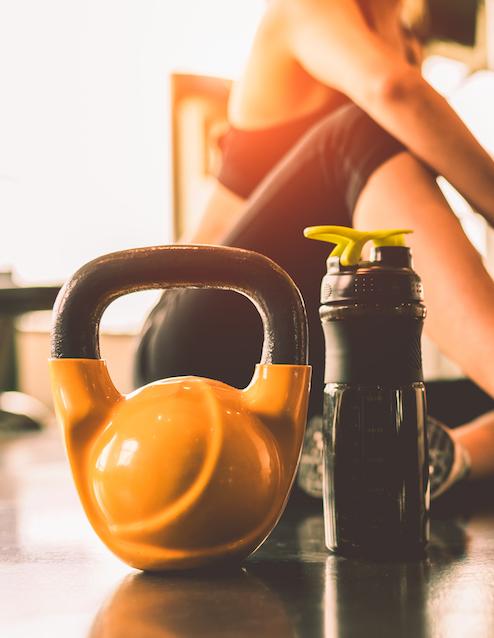 Nahaufnahme von Kettlebell Trainings gerät neben Trainkflasche und Frau im Hintergrund