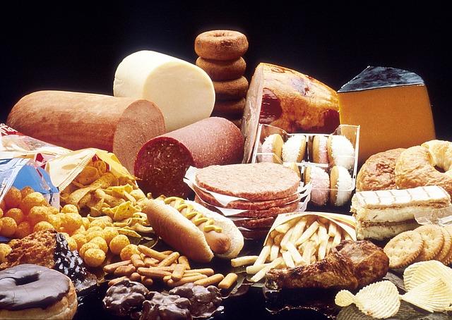 Eine Menge ungesunder Lebensmittel liegen auf einem Tisch verteilt