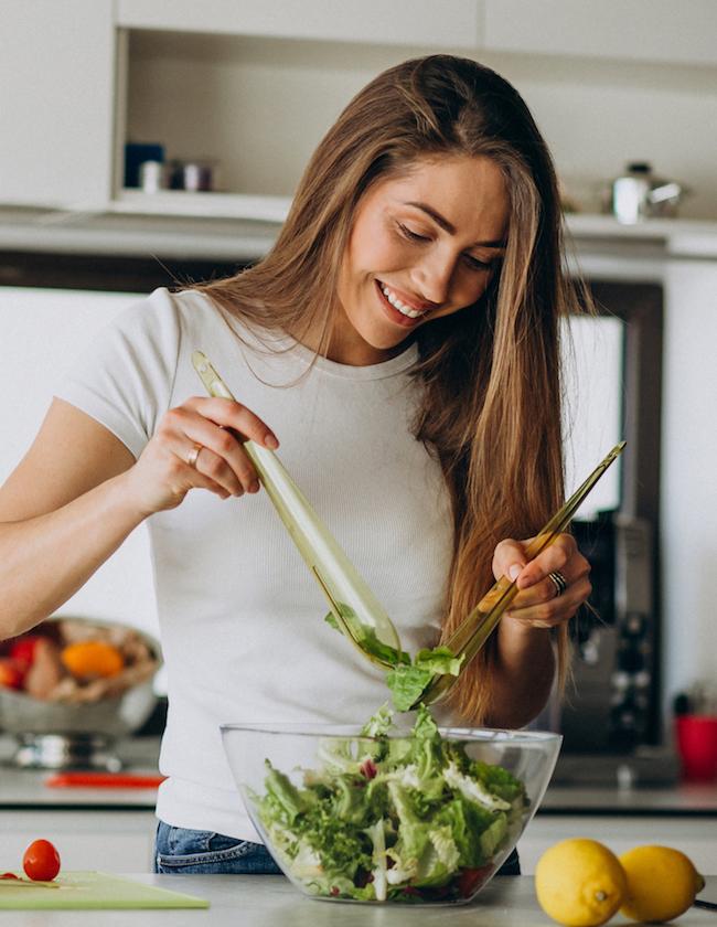 Frau in der Küche richtet Salat an als Plan für gesunde Ernährung