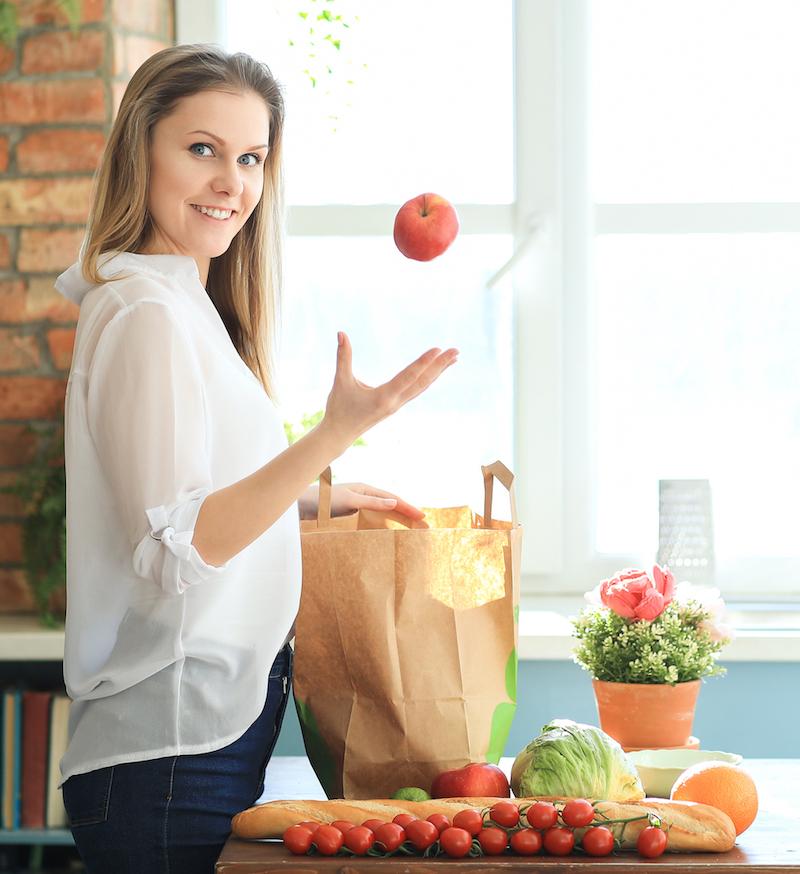 Frau wirft Apfel und steht vor Einkauf von gesunden Lebensmitteln zur gesunden Ernährungsplanung