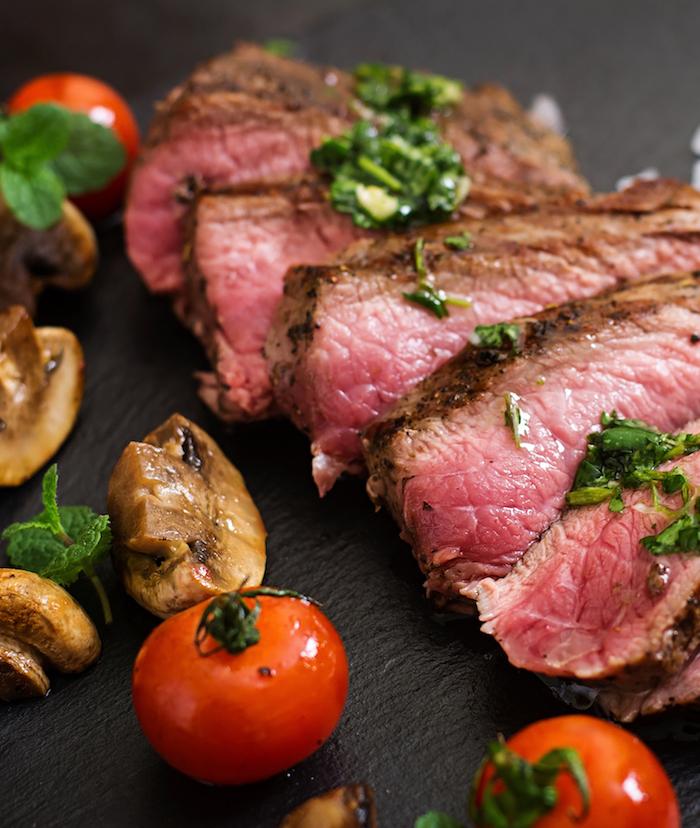 Anschauung von eisenhaltigem Essen als Steak mit Pilzen und Tomaten