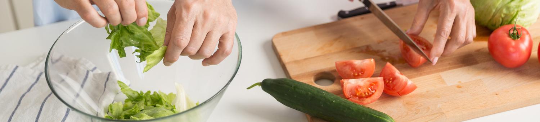 Hände von Frau und Mann in der Küche beim Anrichten von Salat als gesunde Ernährung