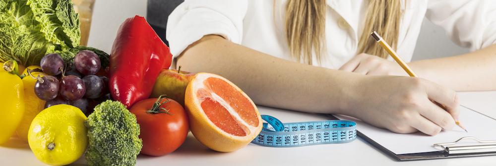 Frau sitzt am Tisch mit gesundem und frischem Obst und Gemüse und schreibt einen Ernährungsplan