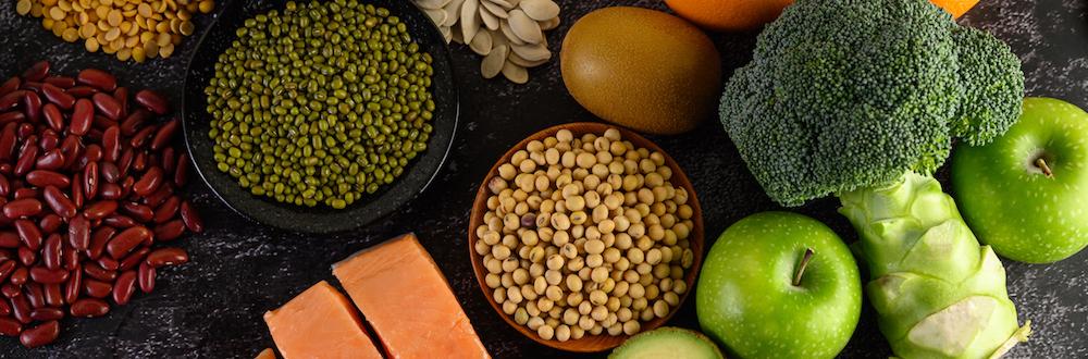 eisenhaltige Lebensmittel auf Tisch mit Lachs, Hülsenfrüchte, und Äpfel