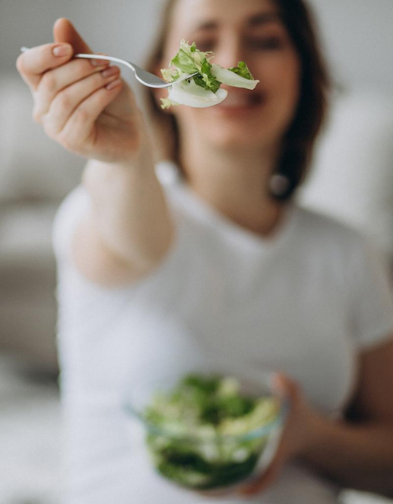 Junge Frau hält Gabel mit Salat und isst Gemüse ohne Kohlenhydrate zur gesunden Ernährung