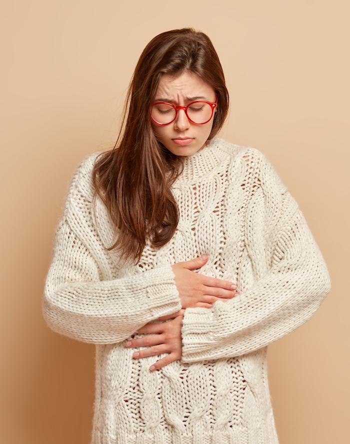 Frau mit Brille weißem Pullover steht vor Wand hält Hände am Bauch