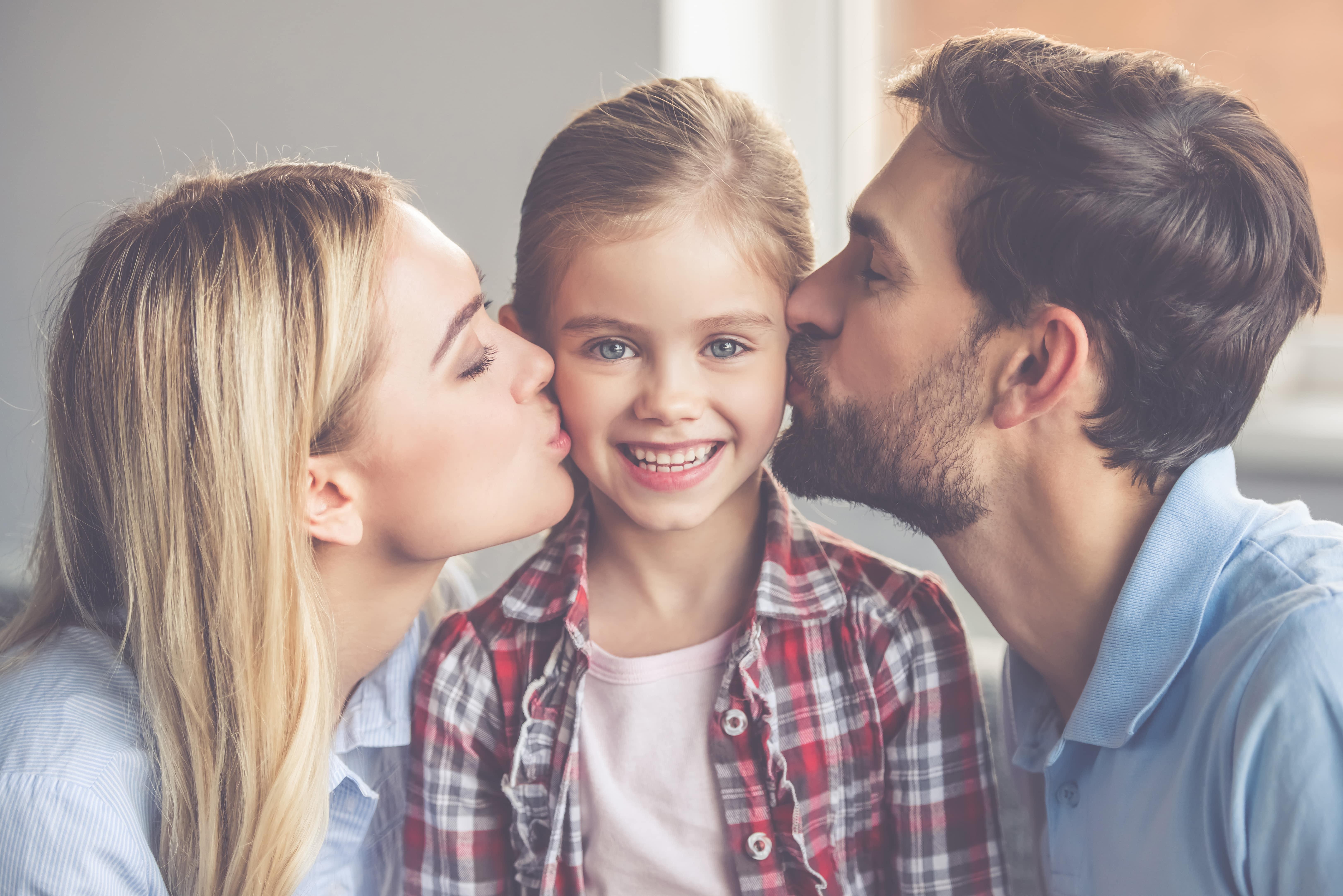 Eltern küssen Tochter
