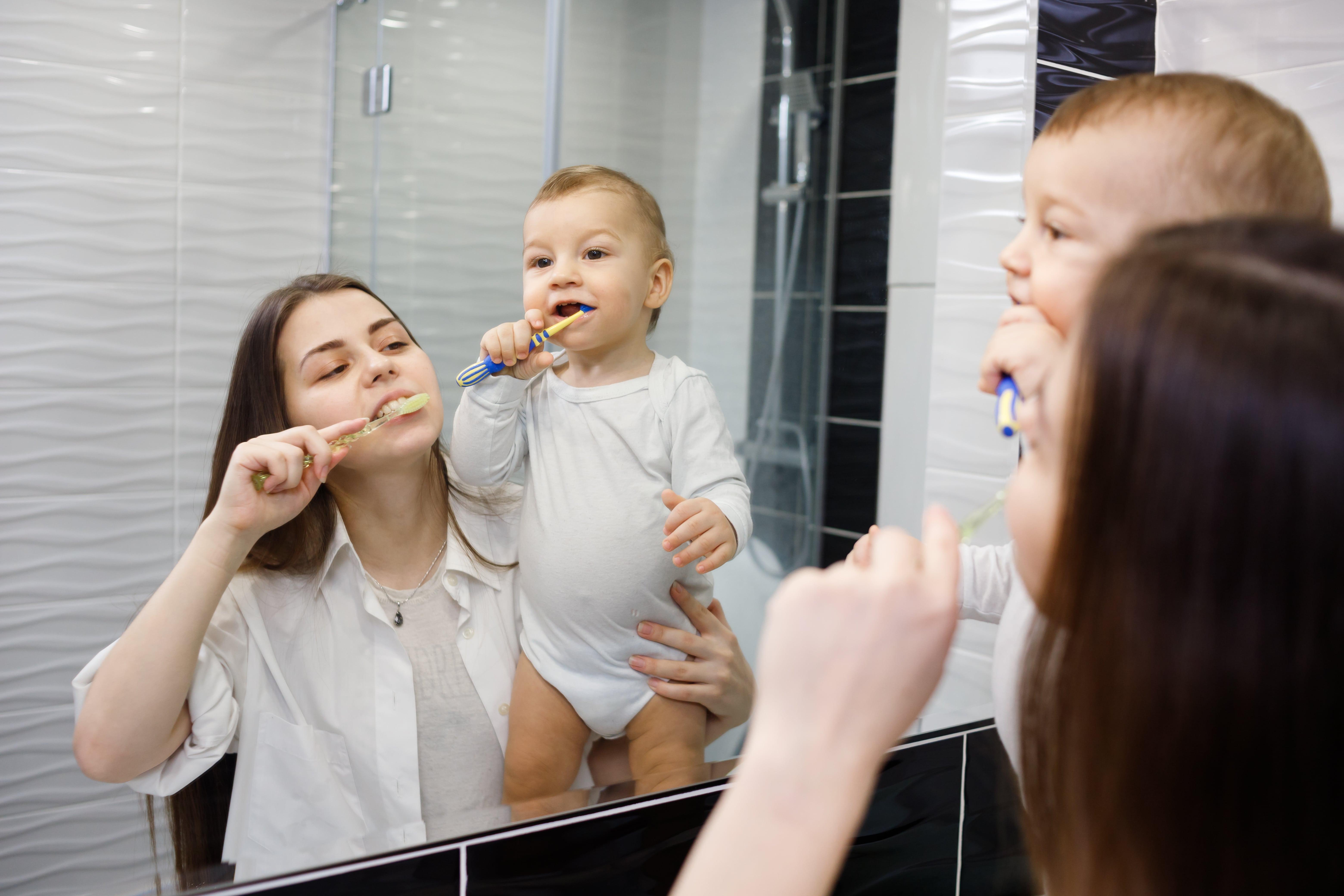 Mutter mit Baby putzen Zähne