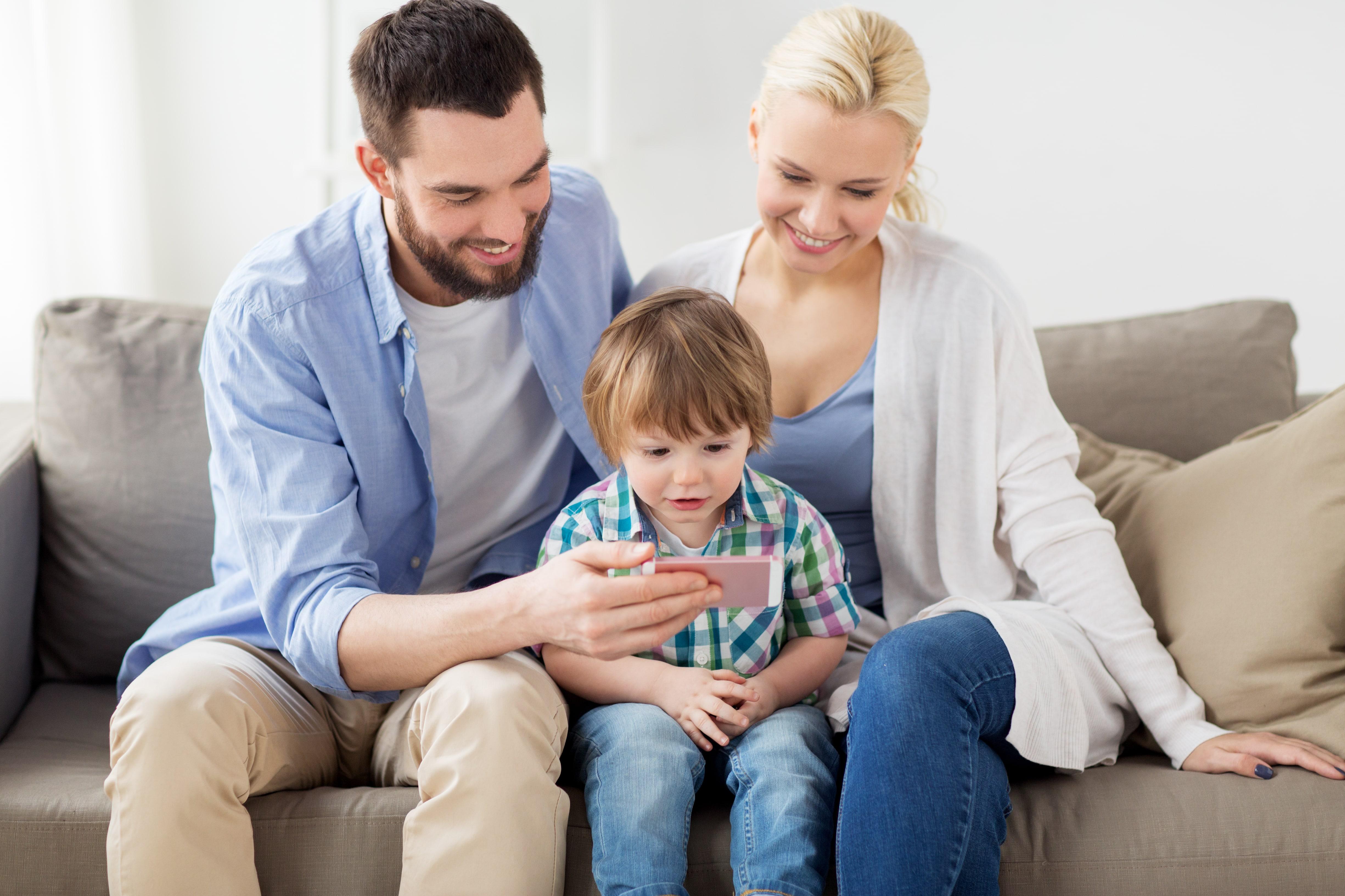 Eltern sitzen mit Kind auf dem Sofa