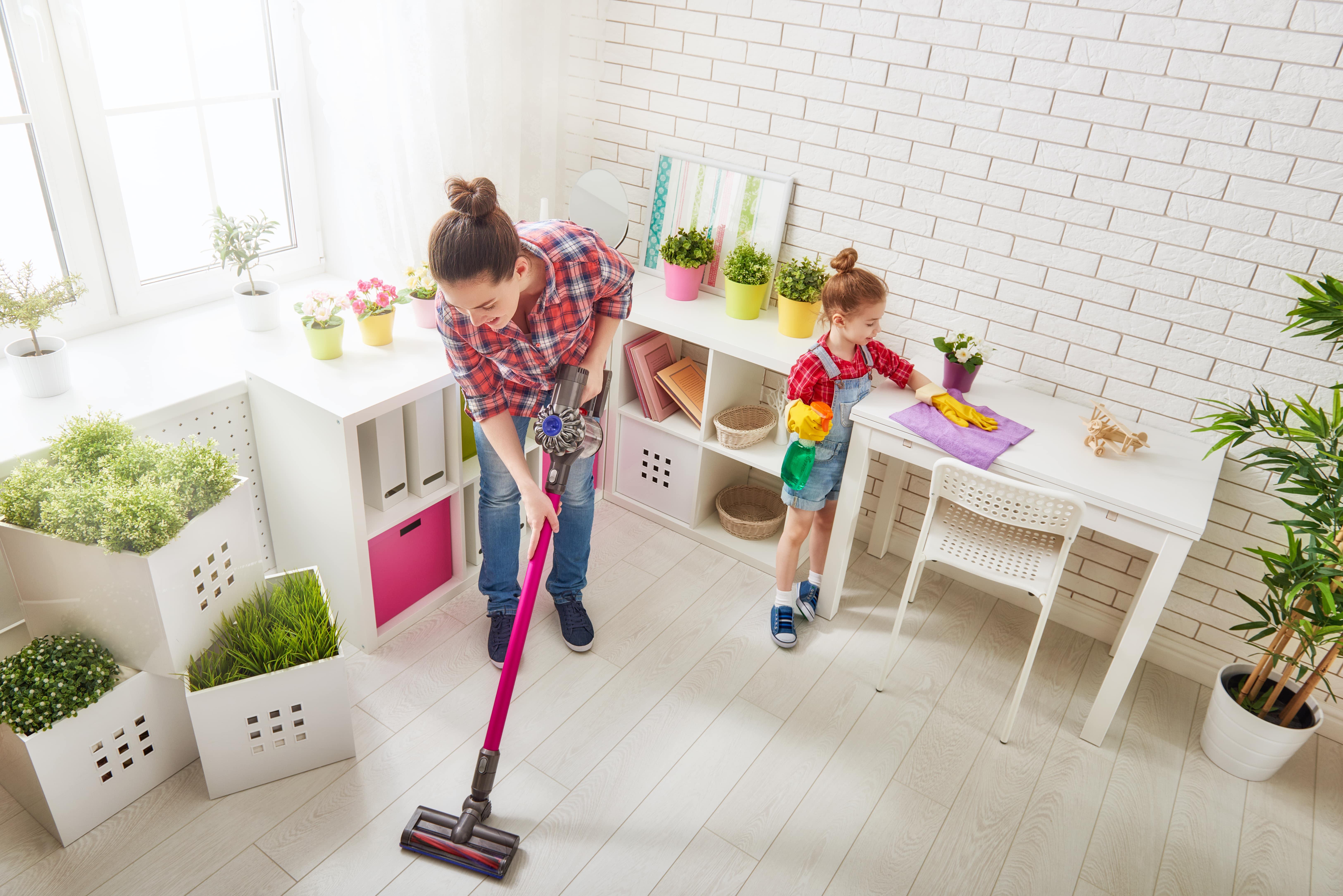 Mutter und Tochter putzen das Zimmer