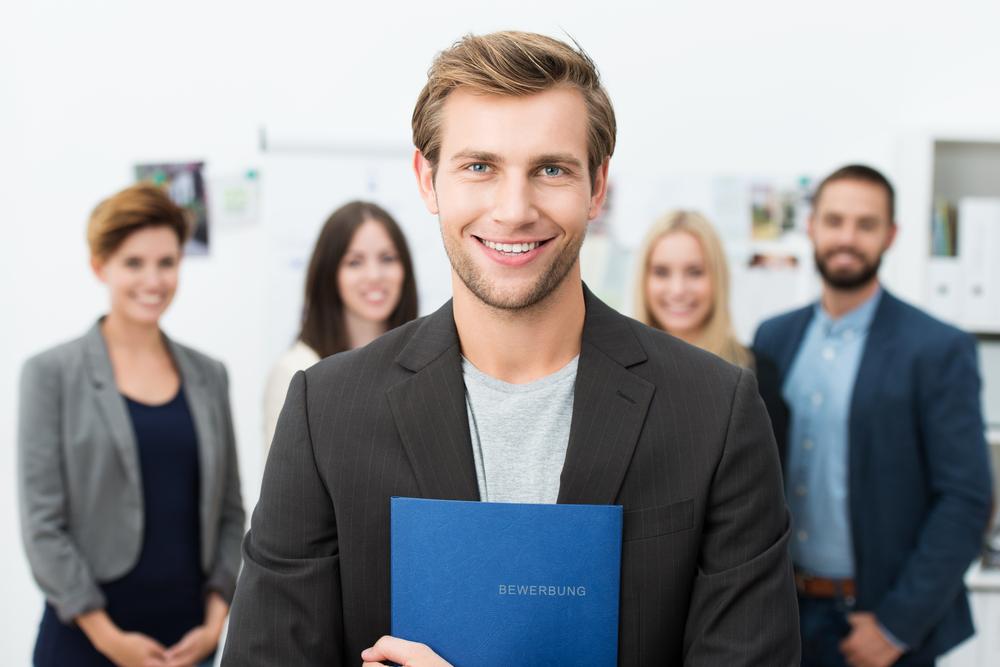 Mann mit Berwerbungsmappe, hinter ihm sind Menschen