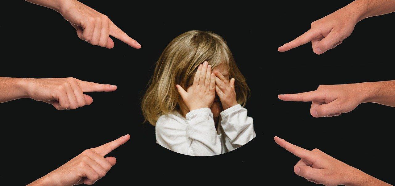 mehrere Finger zeigen auf Mädchen