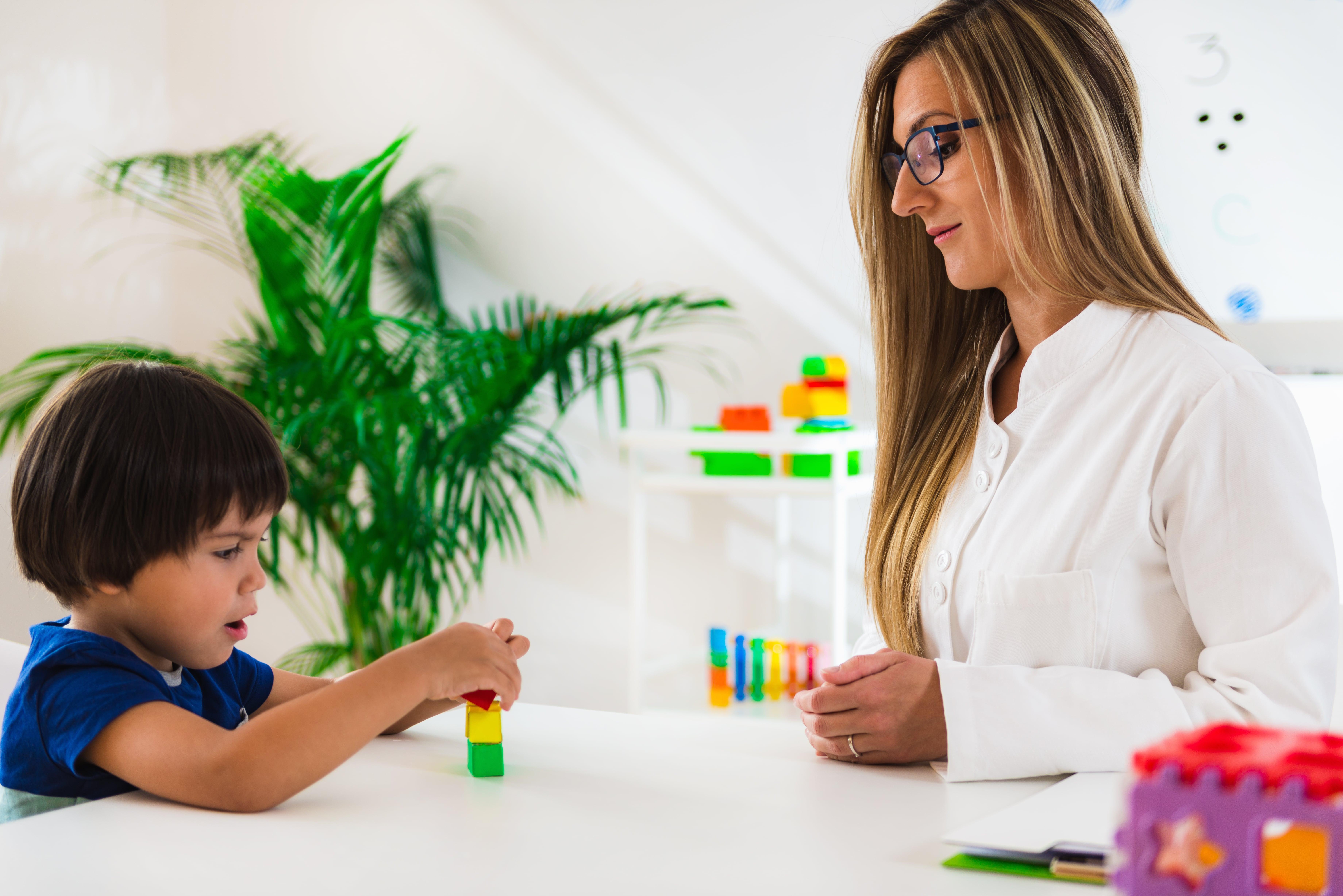 Frau spielt mit Kind am Tisch