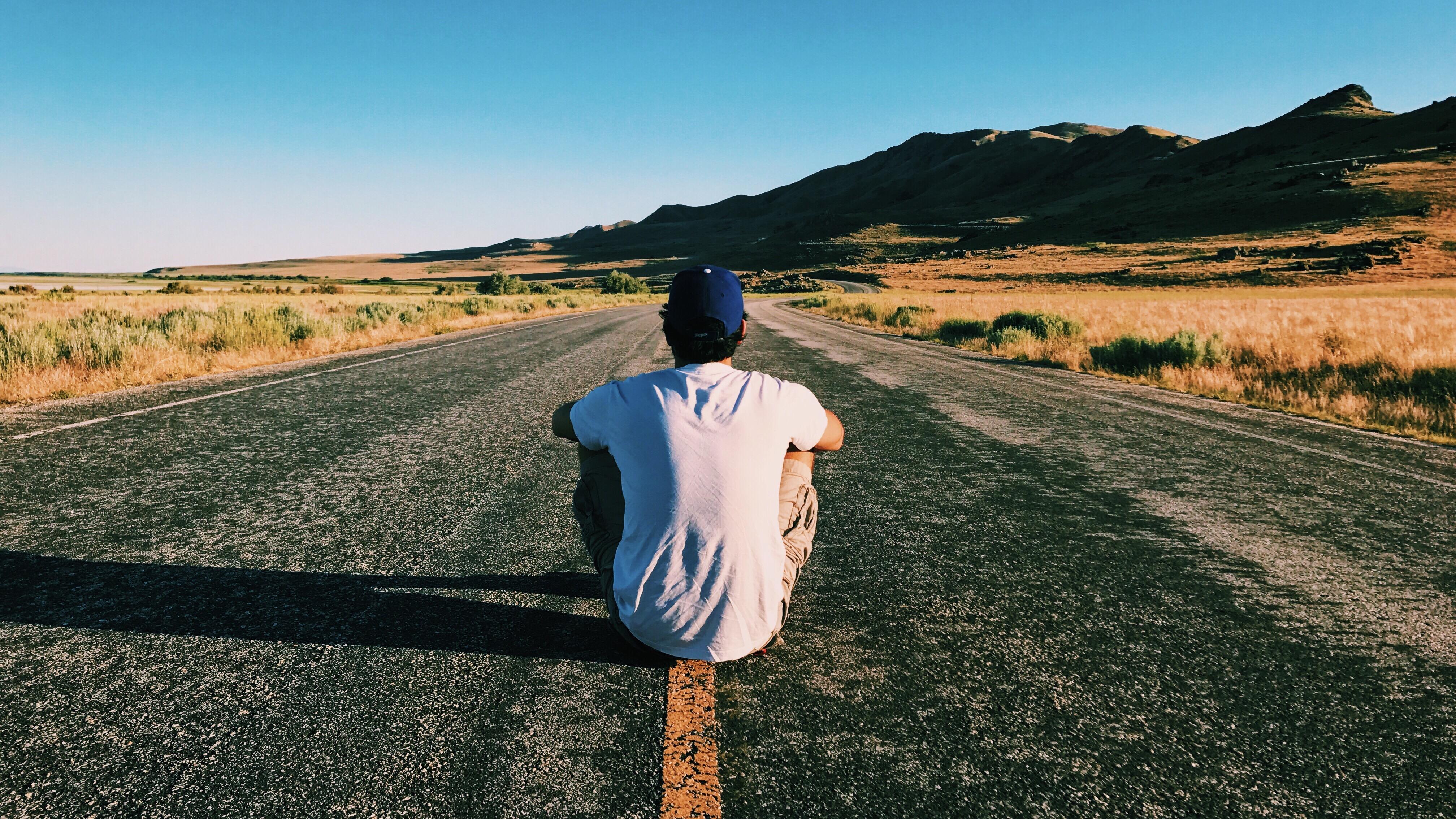Mann sitzt alleine auf der Strasse