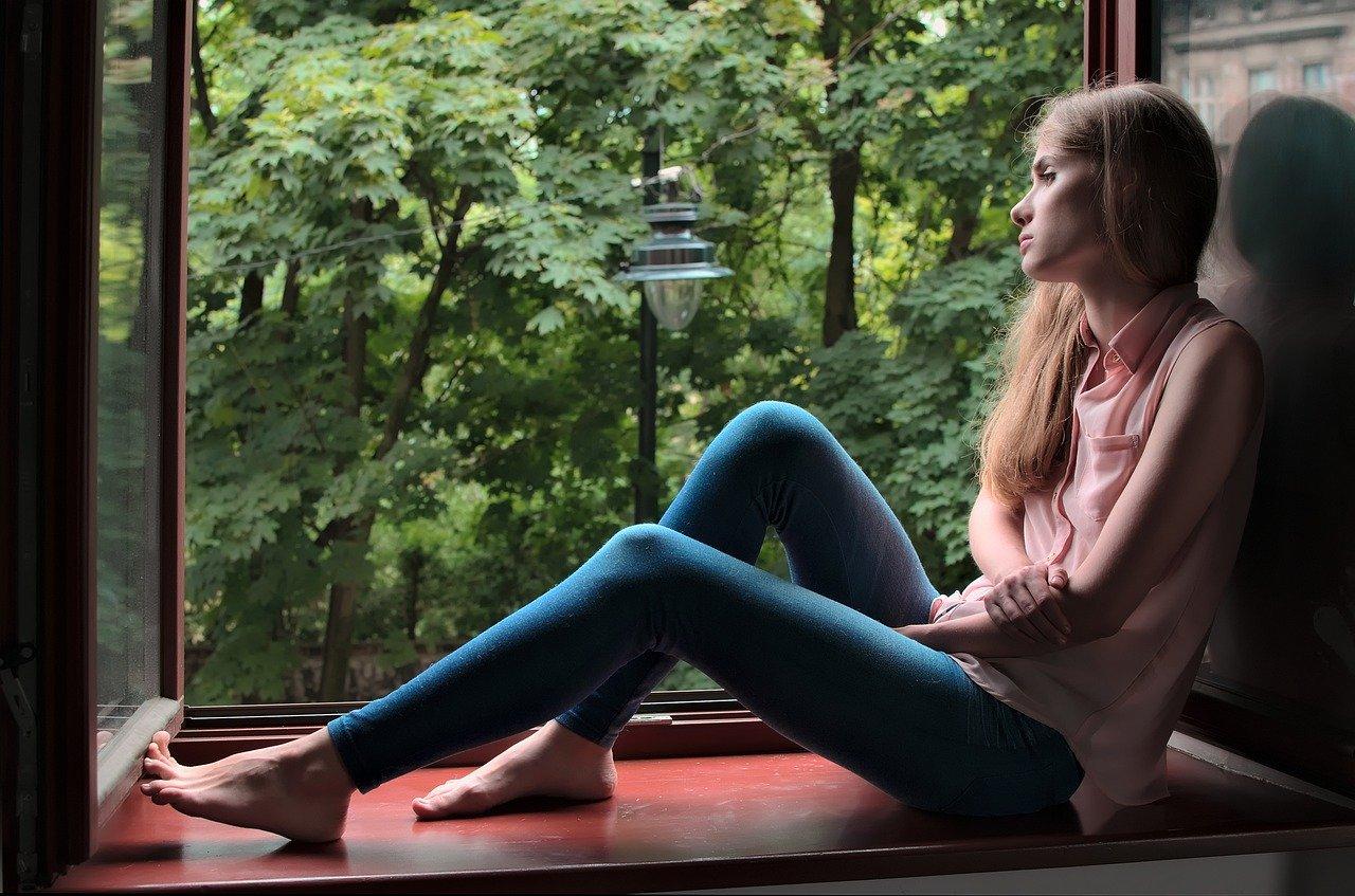 nachdenkliche Frau auf Fensterbrett