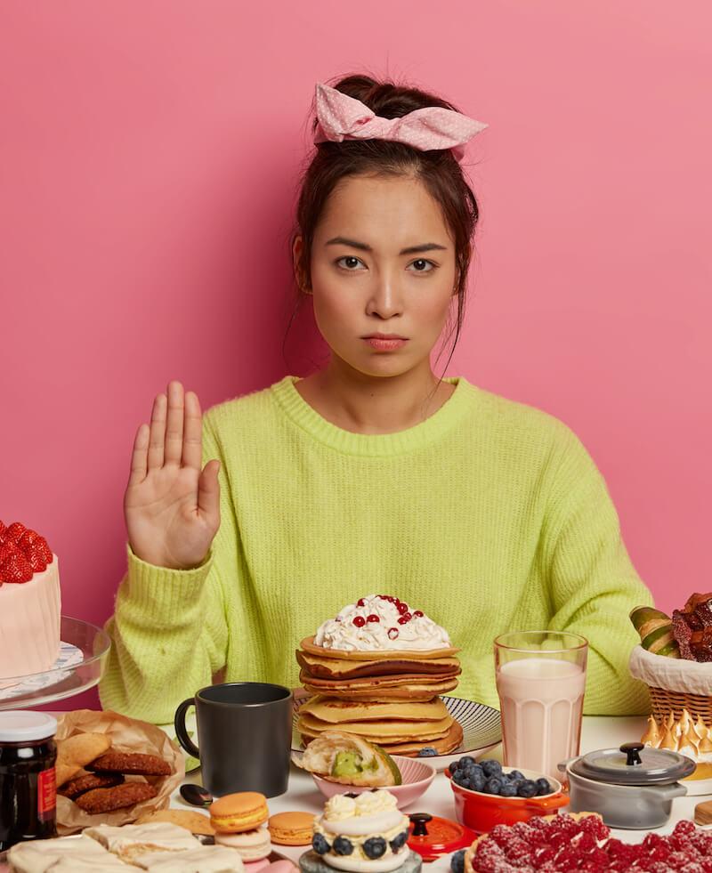 ernst schauende Frau macht stop Geste mit Hand sitz am Tisch süßes und ungesundes Essen