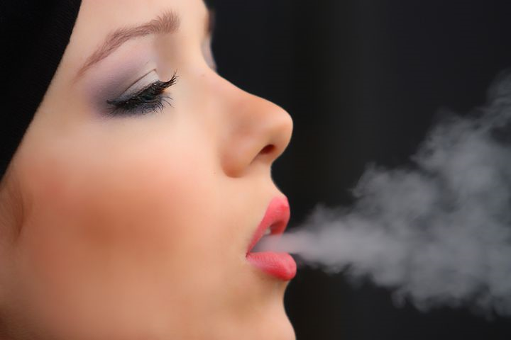 Mädchen raucht eine Zigarette und schluckt dabei Nikotin