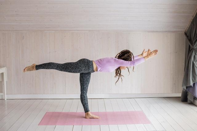 Frau auf Matte übt Bikram Yoga