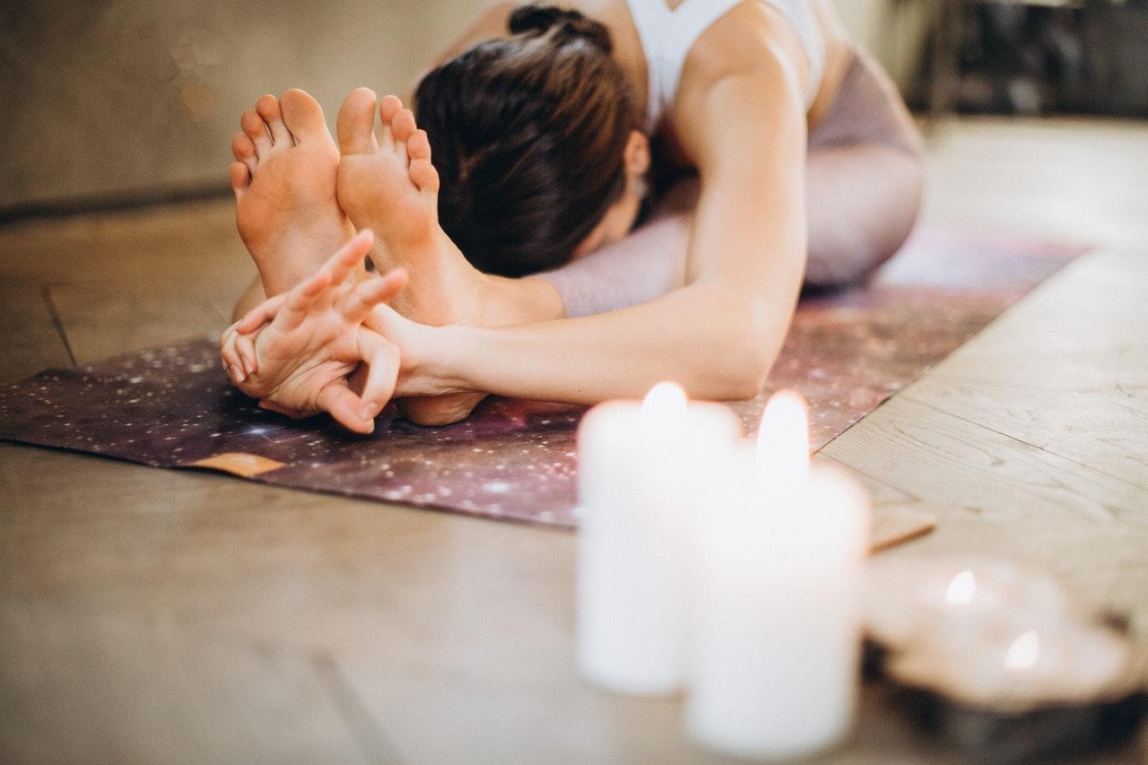 Frau, die Yoga auf dem Boden praktiziert