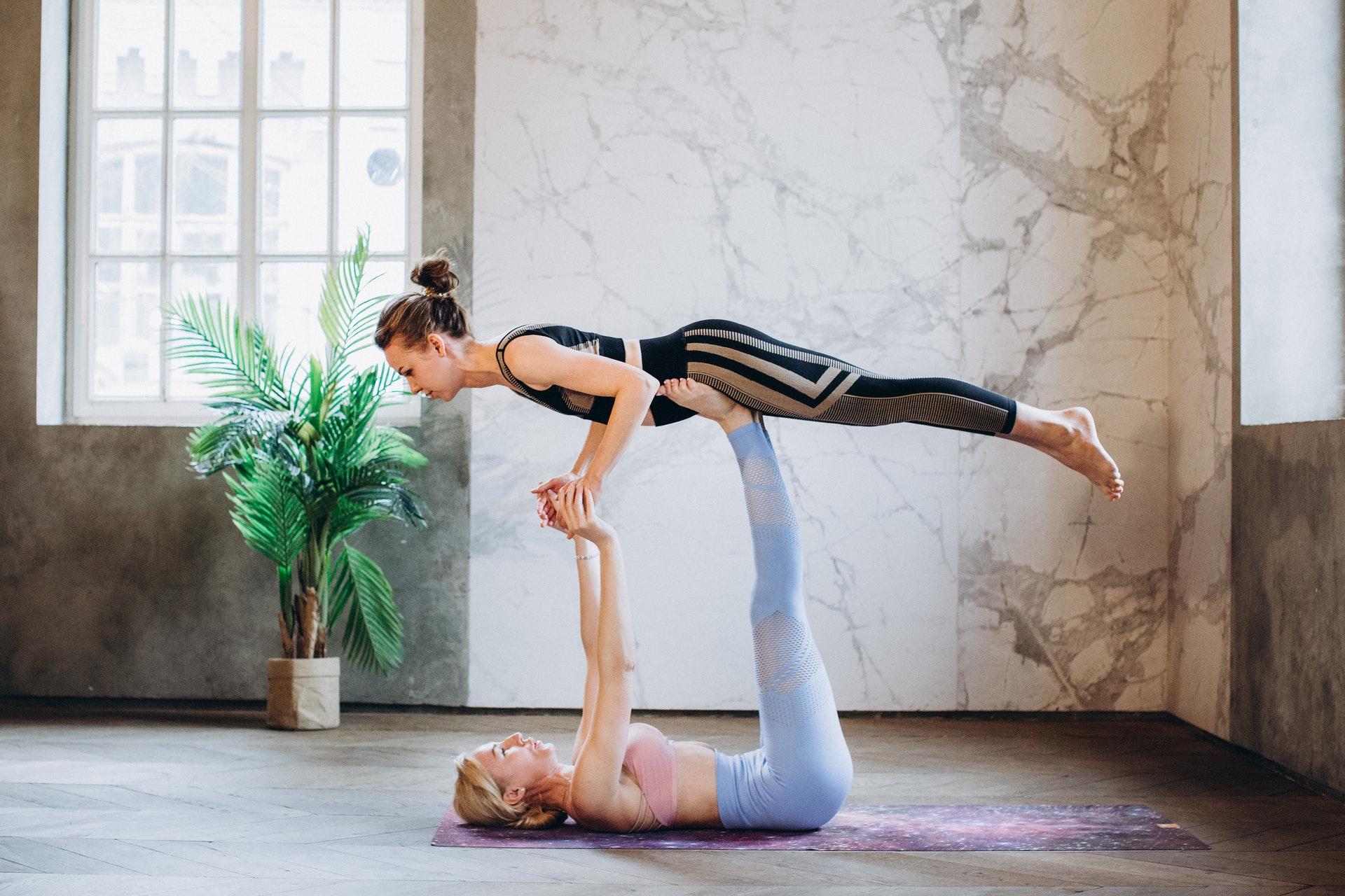zwei frauen in sportbekleidung machen acro yoga