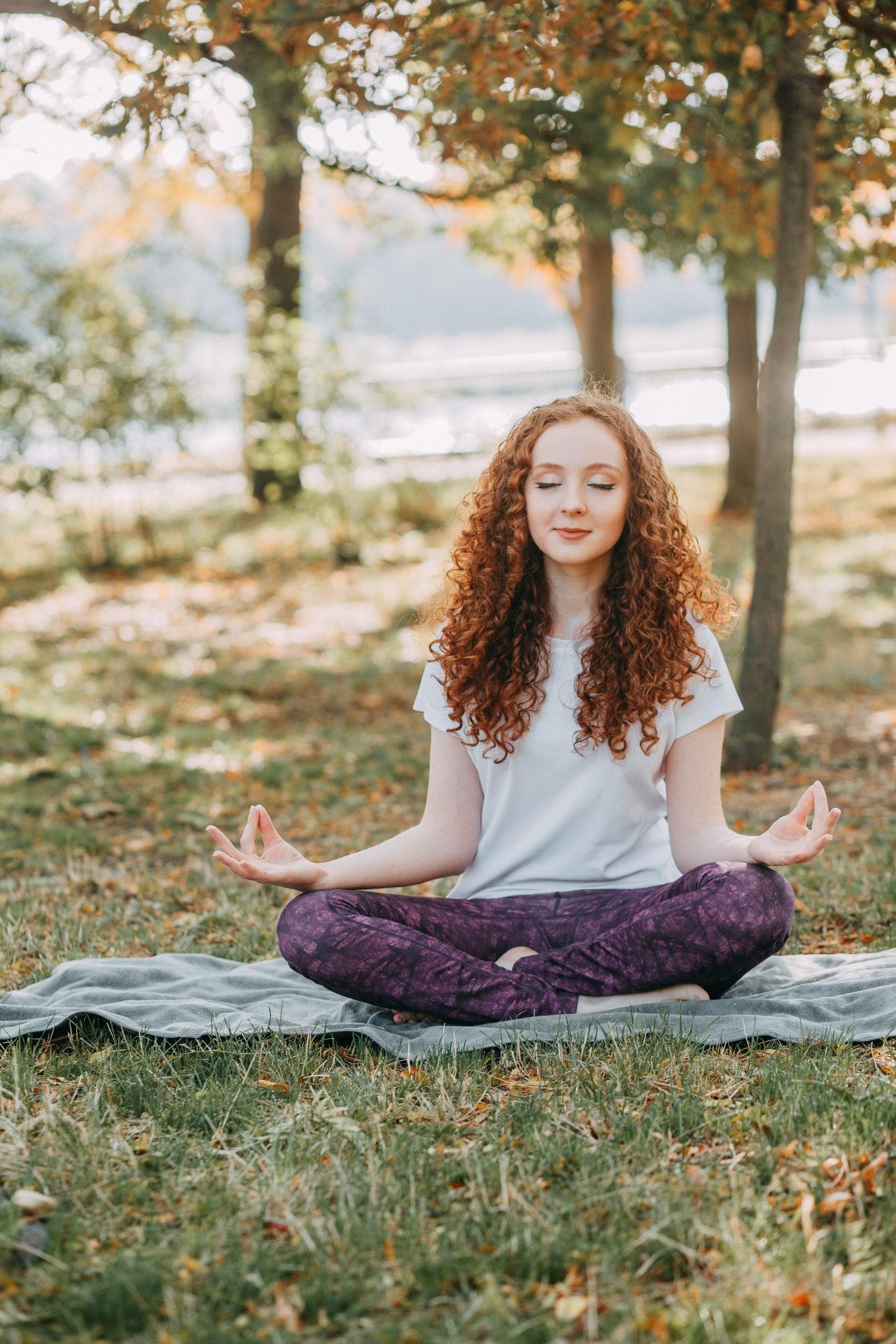 Frau im Schneidersitz draussen am meditieren