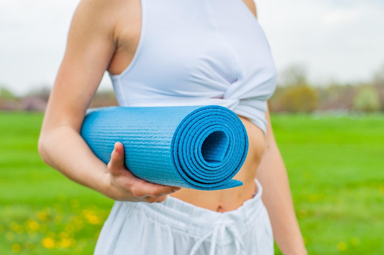 Frau hält Yogamatte im Arm