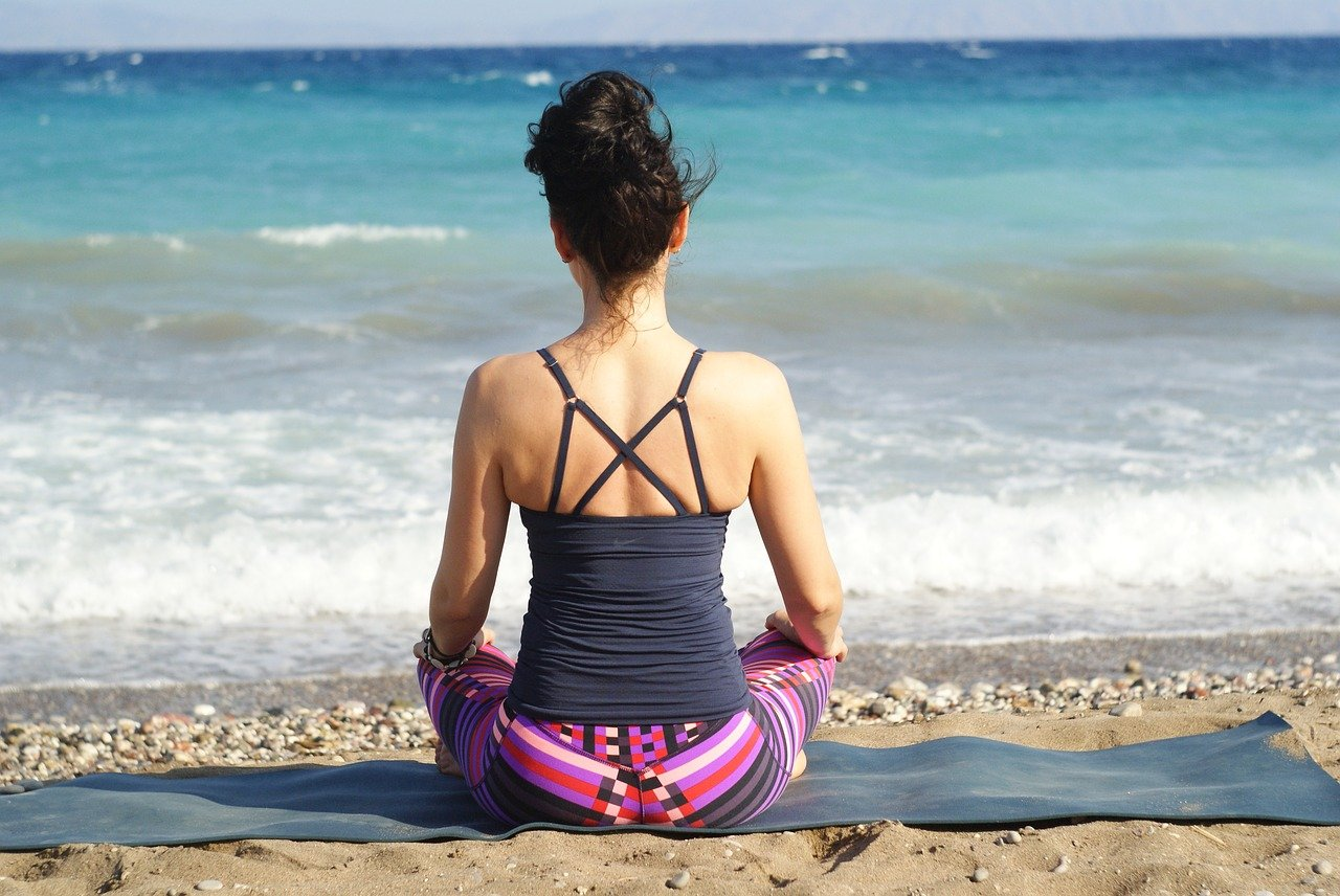 Frau sitzt am Strand und praktiziert Yoga
