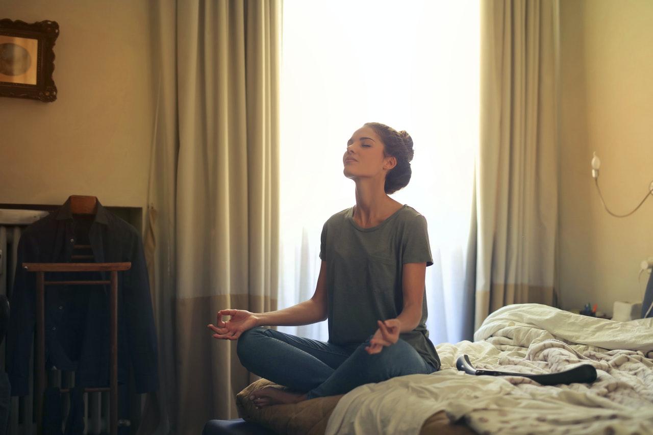 Frau sitzt auf dem Bett und meditiert