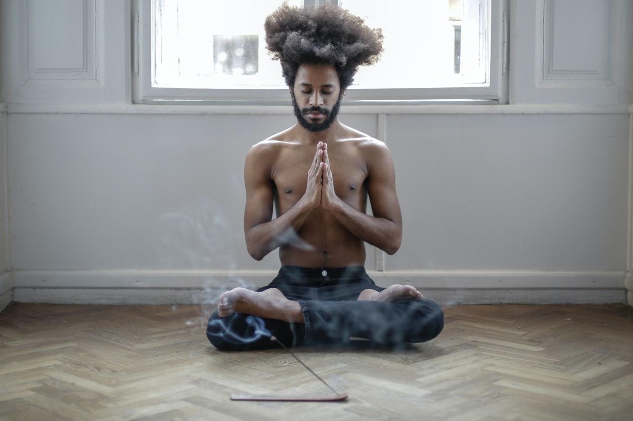 mann sitzt auf dem fussboden und meditiert
