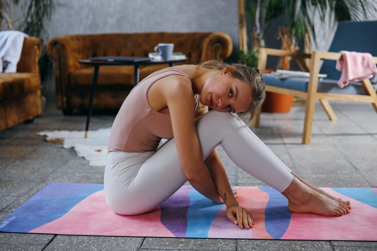 Frau in weissen Leggings sitzt auf der Matte