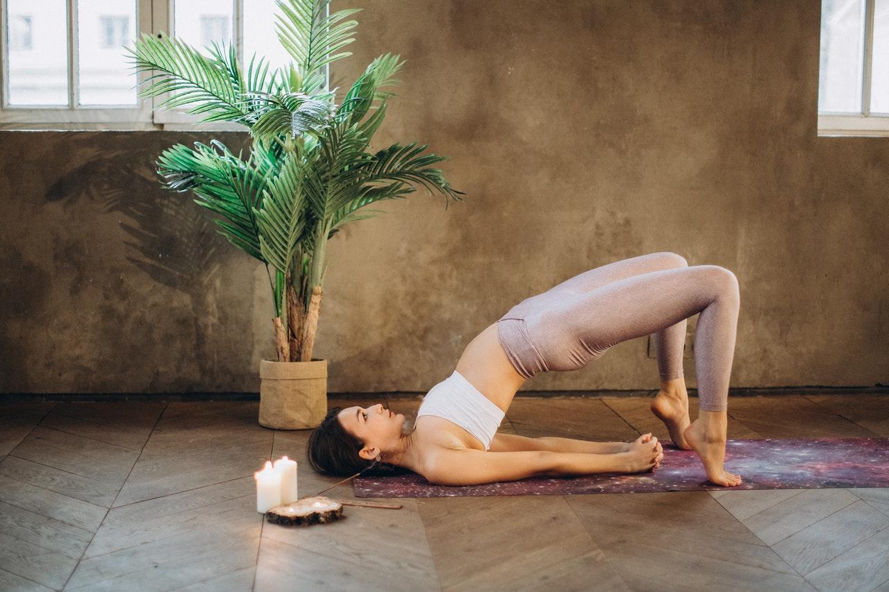 Frau macht Hormon Yoga auf dem Rücken