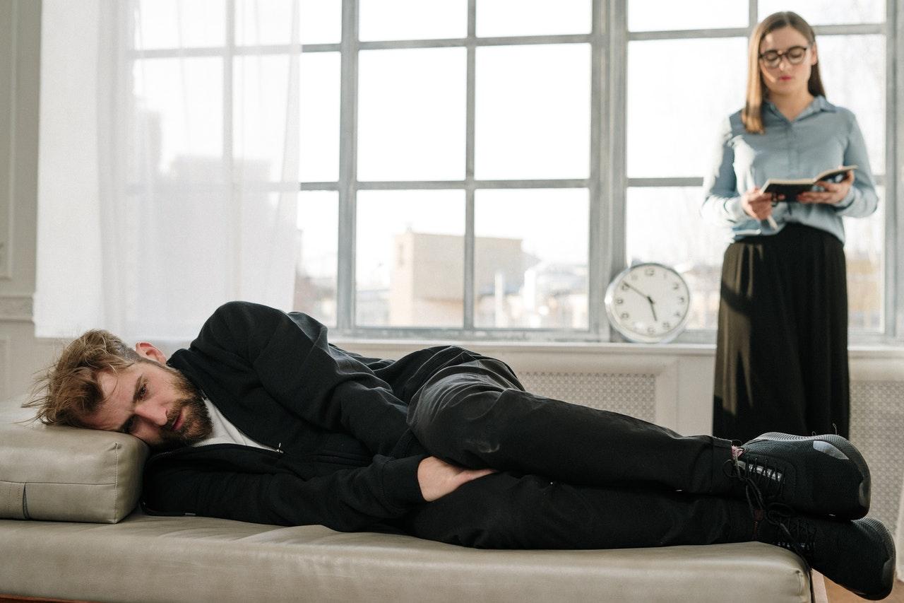 mann liegt auf dem sofa und die frau steht im raum