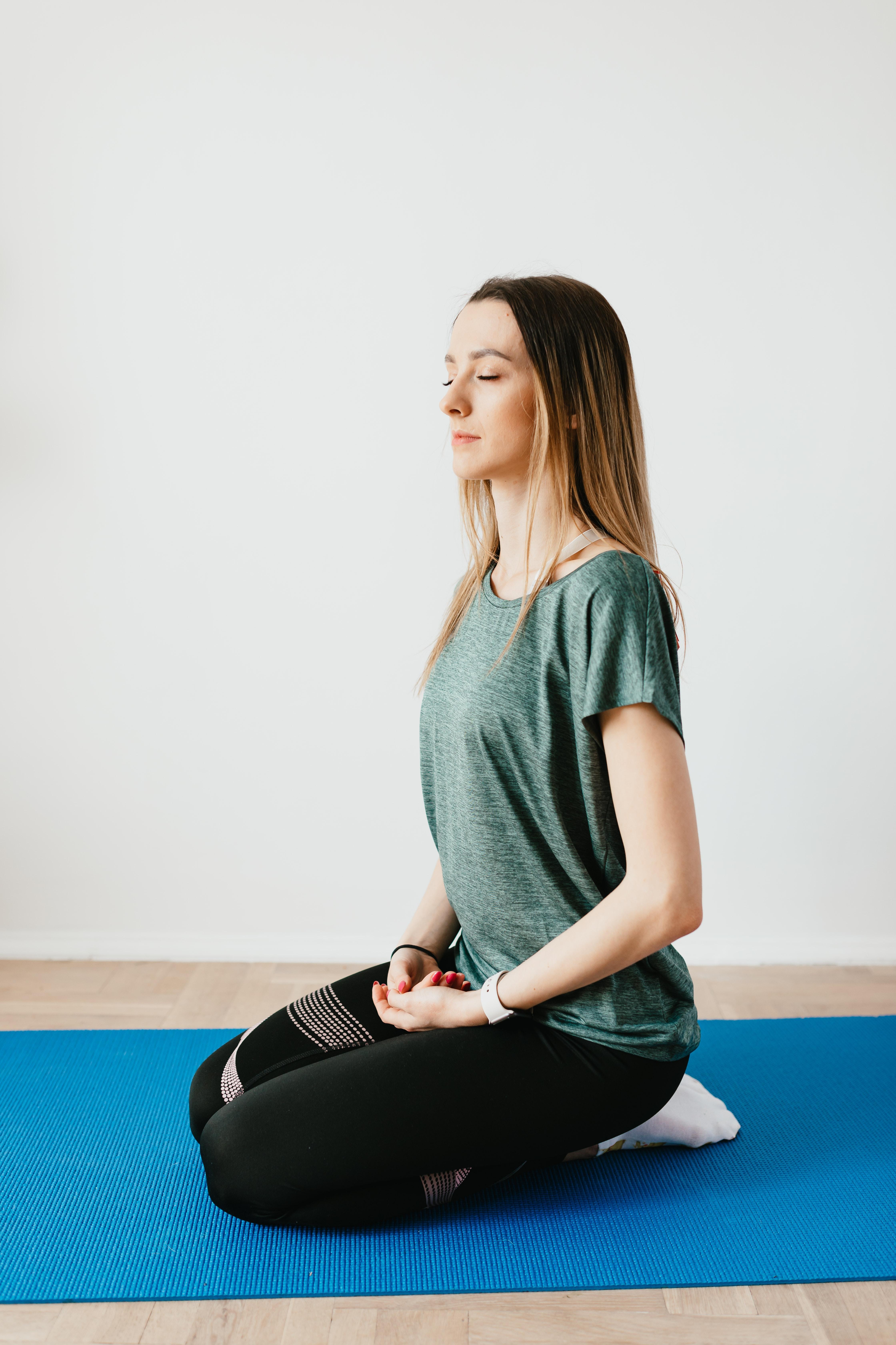 Frau sitzt auf dem Boden und macht Atem Übungen