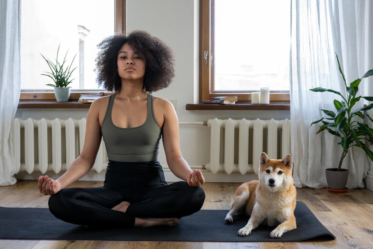 Frau sitzt mit Hund auf dem Boden und meditiert