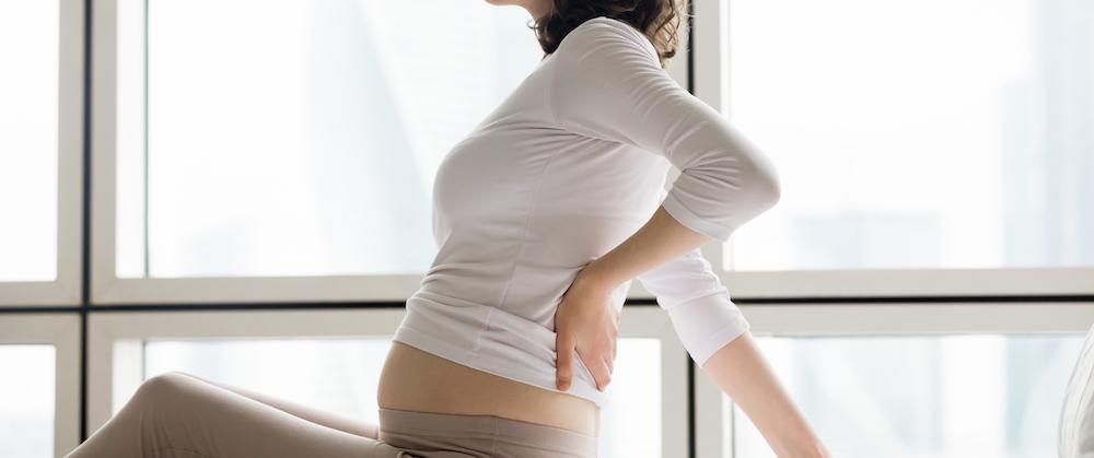schwangere frau sitzt im Bett hat Rückenschmerzen in der Frühschwangerschaft