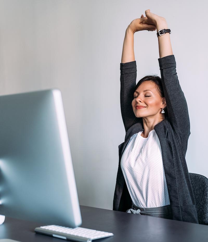 Frau macht stretching übungen am Arbeitsplatz büro gegen Rückenschmerzen