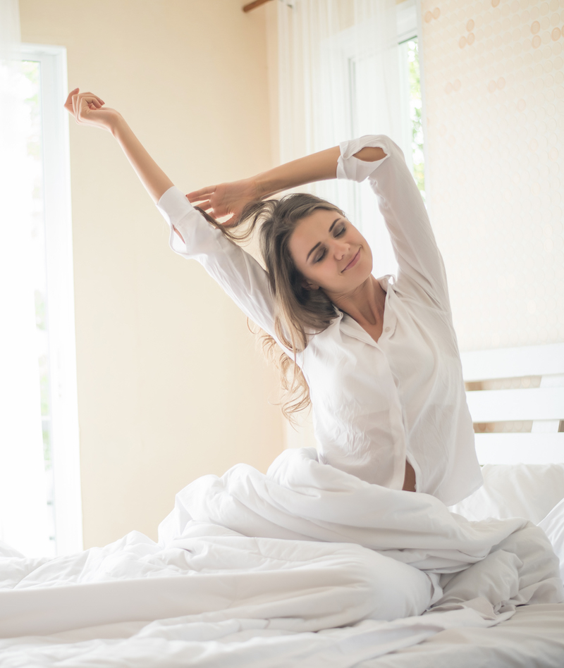 frau im bett streckt sich ohne rückenschmerzen
