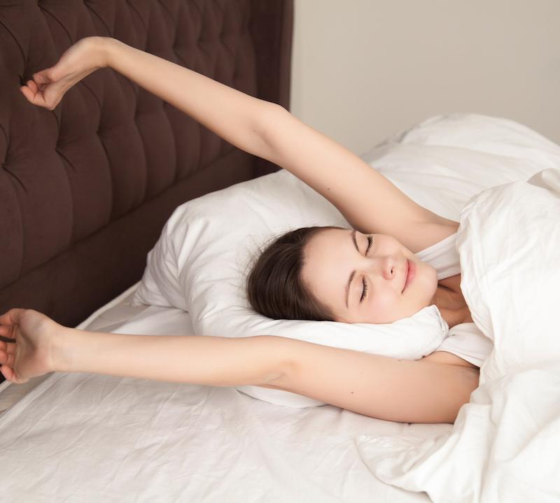 junge frau im bett streckt sich nach erholsamen Schlaf ohne Schlafstörungen