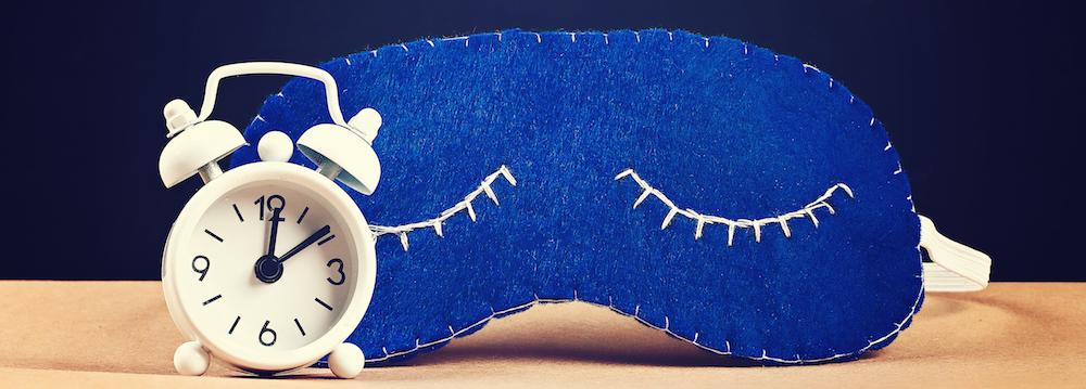 Schlafmaske aus blauem Fliz mit kleiner Weckeruhr als Veranschaulichung von Durchschlafstörungen