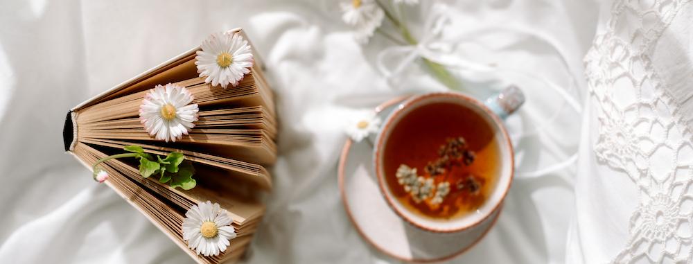 kamille tee zum einschlafen neben buch auf weißem bett