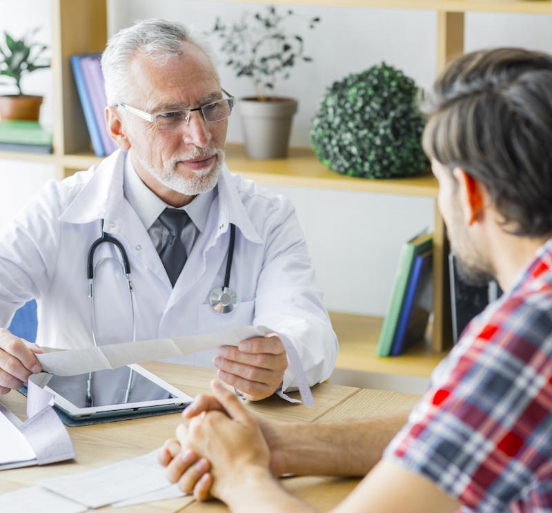 Mann mit Schlafproblemen redet mit älterem Arzt über Schlaftabletten