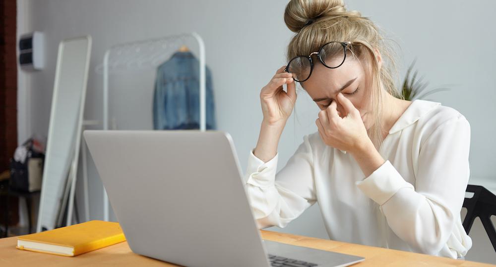 moderne Bürofrau am Computer müde durch Schlafprobleme