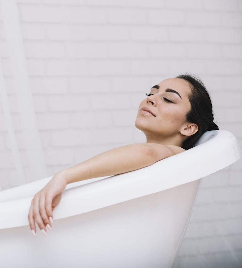 frau liegt entspannt in der badewanne um ihre Schlaflosigkeit zu bekämpfen