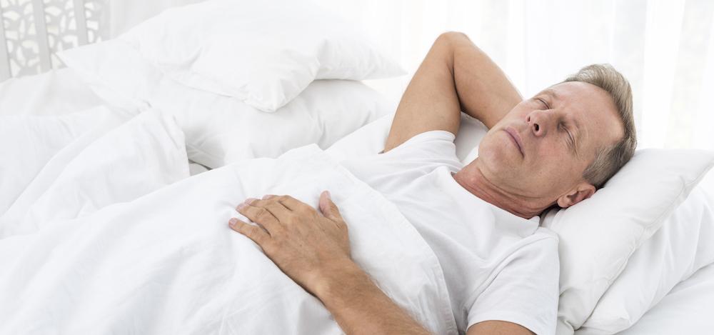 mann mit Schlafapnoe atemproblemen beim Schlafen