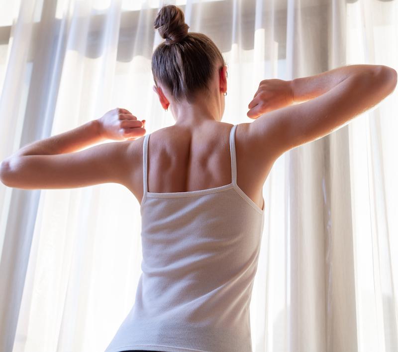 junge Frau streckt sich nach erholsamen Schlaf ohne Durchschlafstörungen