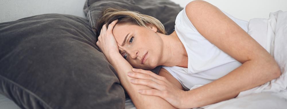 depressive frau liegt im Bett und leidet an schlafstörungen