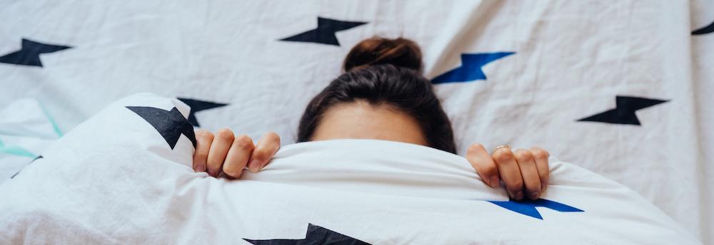 frau liegt in Bett und hält Bettdecke über Gesicht hat Einschlafstörungen
